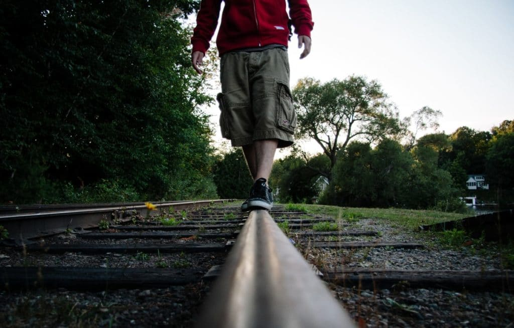 Kid walking on railroad